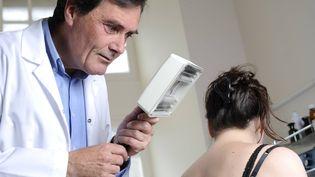Un dermatologue ausculte une patiente dans son cabinet medical. (MAXPPP)