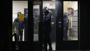 Des policiers entrent dans un immeuble de Villeneuve-la-Garenne (Hauts-de-Seine) lors d'échaufourées avec des habitants, mardi 21 avril. (GEOFFROY VAN DER HASSELT / AFP)
