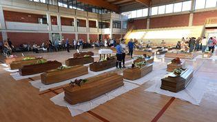 Des cercueils de victimes du séisme alignés dans un gymnase, le 26 août 2016 à Ascoli Piceno (Italie). (ALBERTO PIZZOLI / AFP)