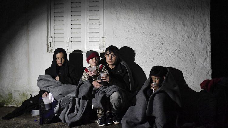 Un nouveau groupe de réfugiés, dont 19 enfants, sont arrivés ce vendredi et patientent contre une maison sur l'île grecque de Lesbos. (LOUISA GOULIAMAKI / AFP)