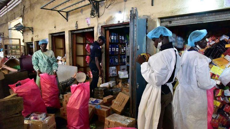 Un policier observe des employés du ministère de la Santé en train de vider des magasins vendant de faux médicaments lors d'une descente le 3 mai 2017 au marché Adjame à Abidjan dans le cadre de la lutte contre les médicaments contrefaits. (Issouf Sanogo / AFP)