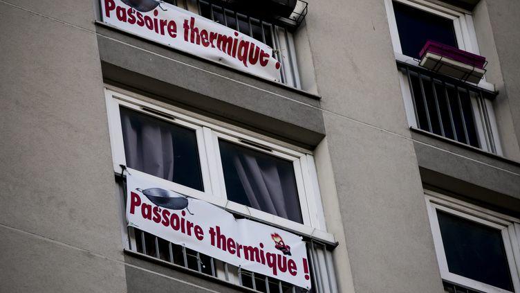 Une banderole accrochee a une fenetre denonce un probleme d isolation thermique dans un logement HLM de la ville de Paris, en 2018 (VINCENT ISORE / MAXPPP)