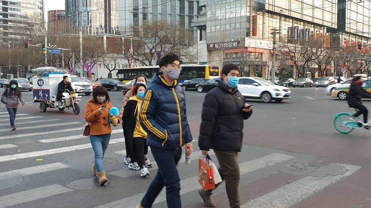 Des personnes portent un masque de protection dans la rue à Pékin en Chine, le 21 janvier 2020. (ANNA RATKOGLO / SPUTNIK)