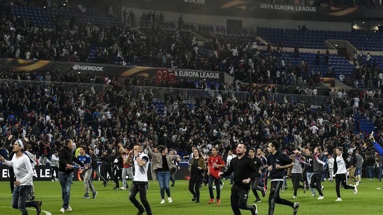 Des supporteurs courent sur la pelouse du Parc OL à Lyon, le 13 avril 2017. (JEFF PACHOUD / AFP)