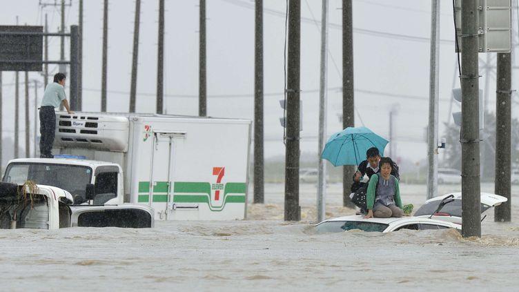 Pris au piège par la brusque montée des eaux, des Japonais attendent l'arrivée des secours sur le toit de leur véhicule, jeudi 10 septembre 2015 à Joso. (KYODO NEWS / AP / SIPA)