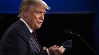 Donald Trump, le président des Etats-Unis, enlève son masque sanitaire lors du débat face à Joe Biden, candidat démocrate, le 29 septembre 2020. (JIM WATSON / AFP)