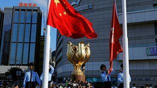 Les militants pro-démocratie se hissent sur la statue dorée représentant une fleur debauhinia, devenue l'emblème deHong Kong(Chine), le 28 juin 2017 (TYRONE SIU / REUTERS)