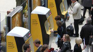 Des voyageurs utilisent des bornes automatiques SNCF, le 16 avril 2010, dans le hall de la gare du Nord, à Paris. (THOMAS COEX / AFP)
