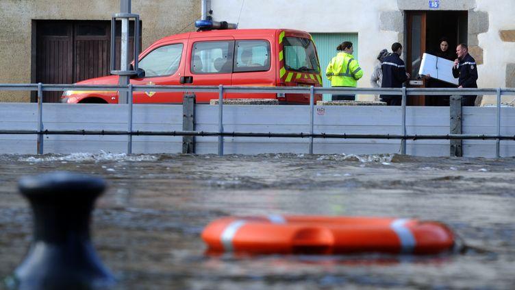Des membres de la sécurité civile discutent avec des habitants de Quimperlé (Finistère), ville noyée par la montée de la Laïta, vendredi 3 janvier. (FRED TANNEAU / AFP)