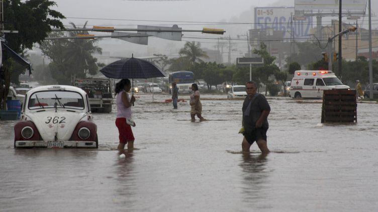 Des habitants d'Acapulco (Mexique) marchent dans les rues inondées de la ville, le 15 septembre 2013. Un ouragan et une tempête tropicale se dirigent vers le Mexique. (JACOBO GARCIA / REUTERS)