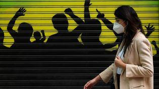 Une femme porte un masque dans la rue, le 4 mai 2020, à Madrid (Espagne). (BURAK AKBULUT / ANADOLU AGENCY / AFP)