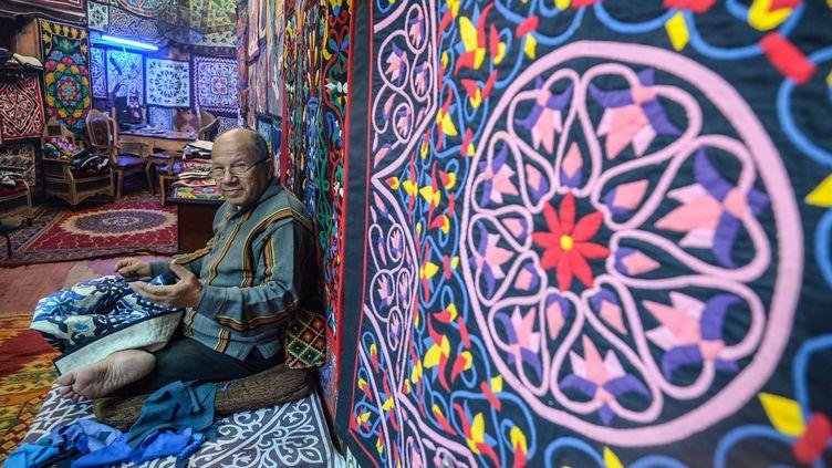 Assis en tailleur dans sa boutique du quartier historique du Caire,Mohsen coud à la main des pièces de tissu en coton sur des toiles aux tailles variables, à but ornemental. (MOHAMED EL-SHAHED / AFP)