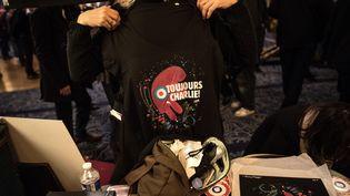 """Une femme montre un teeshirt """"Toujours Charlie"""" pendant le rassemblement aux Folies Bergères, le samedi 6 janvier à Paris. (CHRISTOPHE ARCHAMBAULT / AFP)"""