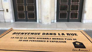 Un paillasson géant a été déroulé dimanche 31 mars par les membres de la fondation Abbé Pierredevant le Ministère de la Cohésion des territoires pour dénoncer les expulsions locatives.  (MANON DERDEVET / RADIO FRANCE)