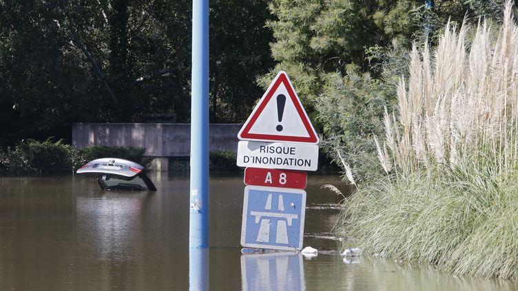 Une voiture abandonnée et presque totalement submergée à Mandelieu, près de l'autoroute. Les intempéries ont fait au moins 7 morts et 1 disparu dans cette commune, selon le bilan provisoire dimanche midi. ( ERIC GAILLARD / REUTERS)