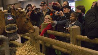Des visiteurs prennent une vache en photo lors du Salon de l'agriculture, le 22 février 2014, à Paris. (CITIZENSIDE / CAROLINE PAUX / AFP)