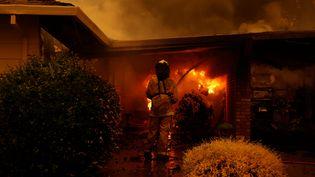 Un pompier éteint une maison en feu lors d'un incendie à Santa Rosa en Californie, le 28 septembre 2020. (STEPHEN LAM / REUTERS)