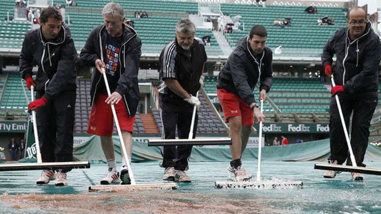 Et pendant que les équipes de Roland-Garros s'affairent pour préserver les courts... (THOMAS COEX / AFP)