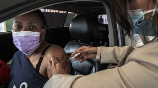 Une femme sud-africaine (à gauche) est assise dans sa voiture alors qu'elle reçoit sa première dose de vaccin Pfizer Covid-19 sur un site de vaccination, à Centurion, près de Pretoria, le 13 août 2021. (LUCA SOLA / AFP)