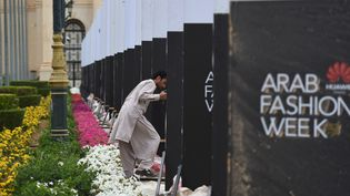 Un ouvrier installe des panneaux avant l'ouverture de la Fashion Week à Riyad, en Arabie saoudite, le 10 avril 2018. (FAYEZ NURELDINE / AFP)