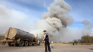 """Le brasier géant pourrait doubler d'ici samedi soir, selon ledirecteur du service des incendies de l'Alberta. Dans cette région productrice de pétrole extrait des sables bitumineux, l'incendie ne pourra pas être éteint """"avant très longtemps"""" à moins qu'il y ait beaucoup de pluie, ajoute-t-il. (COLE BURSTON/ / AFP)"""