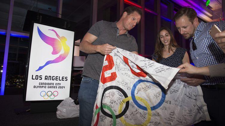 Athlètes et supporteurs avec le drapeau officiel de la présentation du Logo de Los Angeles-2024  (EUGENE GARCIA / EPA)