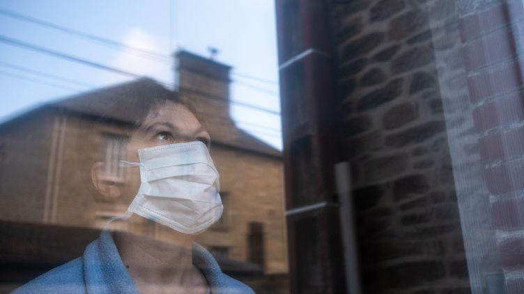 Une personne avec un masque à sa fenêtre dans les Côtes-d'Armor, le 16 mars 2020. (MARTIN BERTRAND / HANS LUCAS)