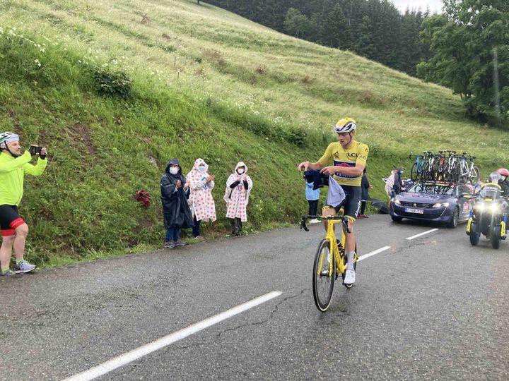 Comme le public derrière lui, Mathieu van der Poel cherche à se protéger de la pluie lors de la traversée pluvieuse des Alpes, ici dans le col de Romme le 4 juillet 2021. (AH)