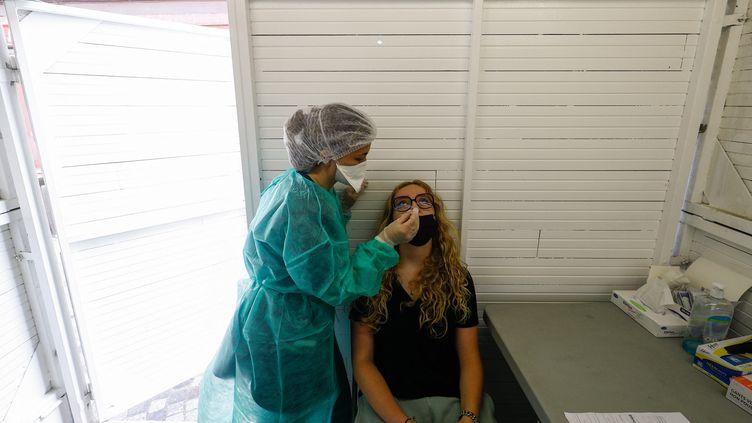 Une employée d'une pharmacie administre un test de dépistage du Covid-19 à Trouville-sur-Mer (Calvados), le 4 août 2021. (SAMEER AL-DOUMY / AFP)