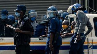 Deux membres du parti d'opposition du Zimbabwe MDC (Mouvement pour un changement démocratique) sont assis à l'arrière d'un camion de police, quelques instants après leur arrestation devant le siège du parti à Harare, le 5 juin 2020. (Jekesai NJIKIZANA / AFP)