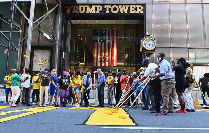 """Le révérend Al Sharpton, le maire de New York Bill de Blasio et sa femme, Chirlane McCray aident à peindre le slogan """"Black Lives Matter"""" (""""Les vies noires comptent"""") devant la tour Trump, le 9 juillet 2020 à New York (Etats-Unis). (ANGELA WEISS / AFP)"""