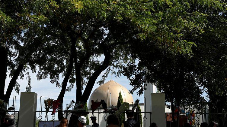 Des personnes réunies devant la mosquée al-Nour de Christchurch (Nouvelle-Zélande), frappée par un attentat, le jour de sa réouverture, le 23 mars 2019. (EDGAR SU / REUTERS)