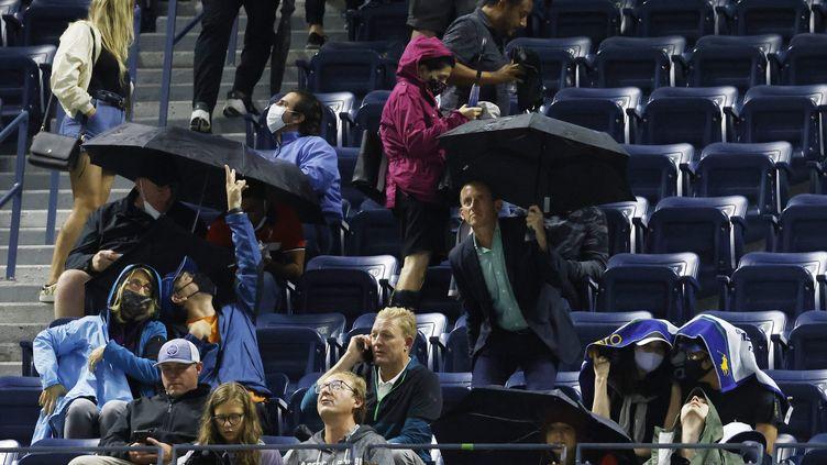Scène incroyable sur le court central Arthur-Ashe de New York : les spectateurs contraints de sortir les parapluies pour s'abriter des intempéries causées par l'ouragan Ida, alors même que le toit du terrain était fermé, le 1er septembre 2021. (MAXPPP)
