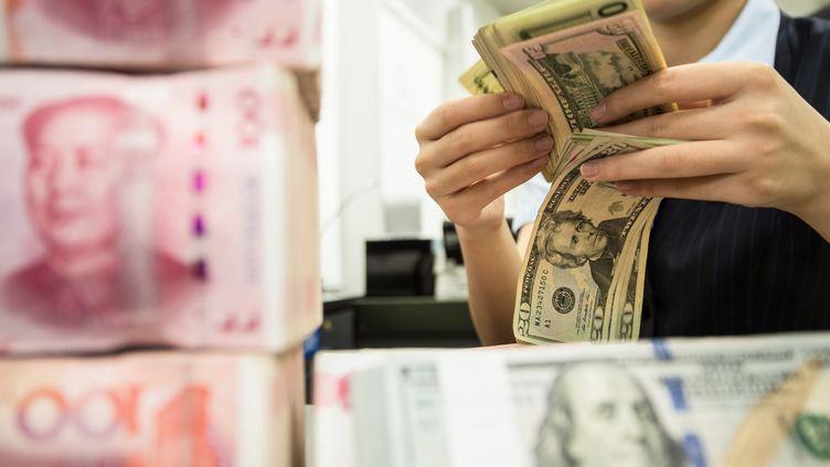 Une employée de banque en Chine compte des billets. (STR / AFP)