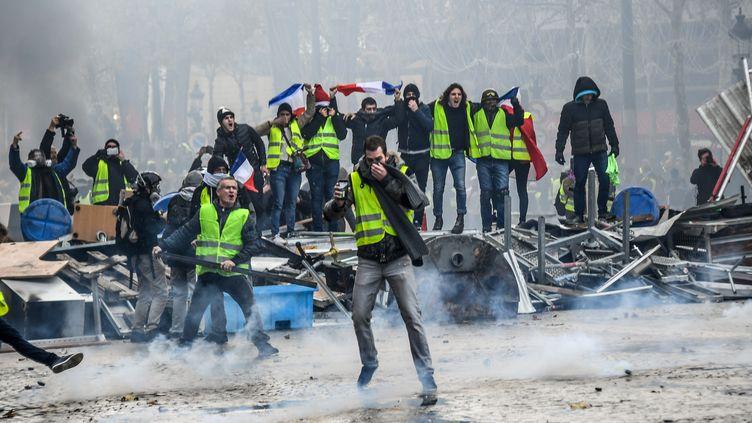 """Des manifestants se réclamant des """"gilets jaunes"""" sur les Champs-Elysées, le 24 novembre 2018 à Paris. (BERTRAND GUAY / AFP)"""