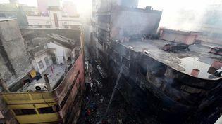 Plusieurs bâtiments d'un quartier historique de Dacca, la capitale du Bangladesh, ravagés par les flammes au lendemain d'un incendie qui a tué au moins 69 personnes, dans des immeubles d'habitation où se trouvaient des produits chimiques. (MUNIR UZ ZAMAN / AFP)