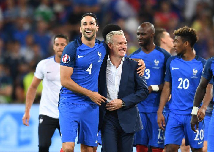 Didier Deschamps dans les bras d'Adil Rami, devant d'autres remplaçants réjouis, Kingsley Coman et Eliaquim Mangala, juste après la victoire des Bleus en demi-finale de l'Euro contre l'Allemagne, le 7 juillet 2016 à Marseille (Bouches-du-Rhône). (FEDERICO GAMBARINI / DPA / AFP)