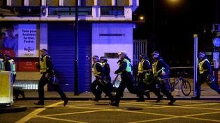 Des policiers courent vers le lieu d'une attaque, à Londres (Royaume-Uni), le 3 juin 2017. (HANNAH MCKAY / REUTERS)