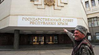"""Un habitant de Simferopol (Crimée) se réjouit que ce qui étaitappelé le """"Conseil suprême"""" soit devenu le """"Conseil d'Etat de la République de Crimée"""". (TARAS LITVINENKO / RIA NOVOSTI / AFP)"""
