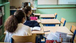 Dans une salle de classe d'une école de Vesoul (Haute-Saône), des tables vides sont placées à côté des élèves afin de garantir le respect de la distanciation physique, le 14 mai 2020. (JEAN-FRANÇOIS FERNANDEZ / RADIO FRANCE)