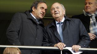 Michel Platini, président de l'UEFA, et Sepp Blatter, président de la FIFA, photographiés ici ensemble le 23 mai 2013 à Londres (Royaume-Uni). (IAN KINGTON / AFP)