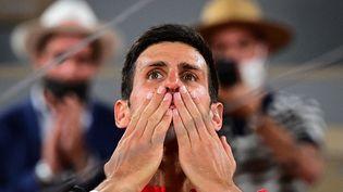 Le Serbe Novak Djokovic, ému après sa victoire face à Rafael Nadal en demi-finale de Roland-Garros, le 11 juin 2021. (MARTIN BUREAU / AFP)