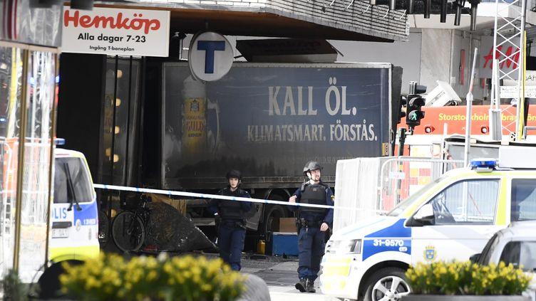 La police suédoise dresse un cordon de sécurité autour du camion qui a renversé des piétons avant de s'encastrer dans une magasin, à Stockholm, vendredi 7 avril 2017. (JONATHAN NACKSTRAND / AFP)