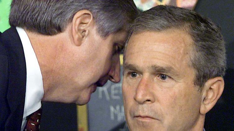 Andrew Card apprend à George W. Bush en visite dans une école primaire qu'une attaque a eu lieu à New York, le 11 septembre 2001. (PAUL J. RICHARDS / AFP)