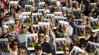 Quelque 2 000 portraits d'Hervé Gourdel, ainsi qu'un millier de roses blanches, ont été distribués par la mairie de Nice, organisatrice de cette marche en accord avec la famille, le 27 septembre 2014. (VALERY HACHE / AFP)