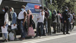 Des migrants attendent leur transfert vers la Grèce continentale, depuis l'île de Lesbos, le 28 septembre 2020. (MANOLIS LAGOUTARIS / AFP)