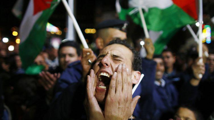 Un Palestinien célèbre l'adoption par l'ONU d'une résolution accordant à la Palestine le statut d'Etat observateur, le 29 novembre 2012 à Ramallah (Cisjordanie). (MARKO DJURICA / REUTERS)