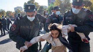 Des policiers arrêtent des manifestants qui défilent à Erevan, en Arménie, contre l'accord de fin des hostilités dans le Haut-Karabakh, le 11 novembre 2020. (ILIYA PITALEV / SPUTNIK / AFP)