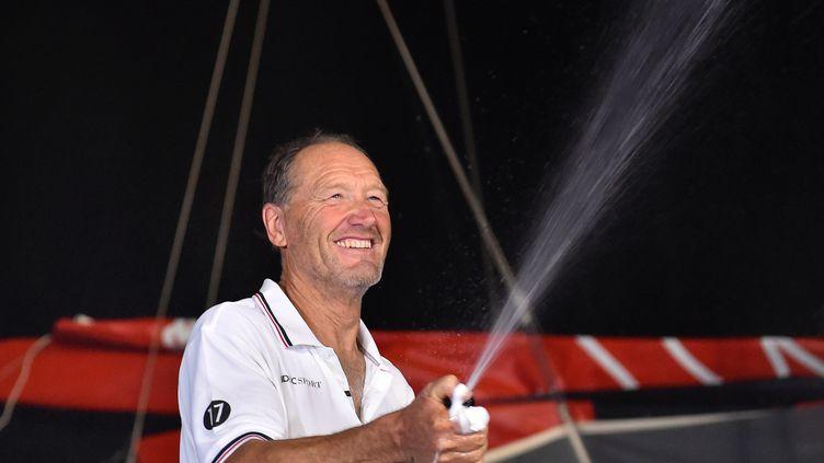 Francis Joyon sabre le champagne après sa victoire sur la Route du Rhum, le 11 novembre 2018. (LOIC VENANCE / AFP)