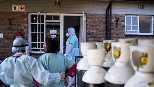 Un soignant aide une patiente du Covid-19 à regagner sa chambre dans un centre de soins Covid à Norwood, Johannesburg, le 12 juillet 2021. (EMMANUEL CROSET / AFP)